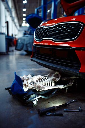 Human skeleton lying under the vehicle, car service station, problematic vehicle concept. Automobile checking and inspection, professional diagnostics and repair