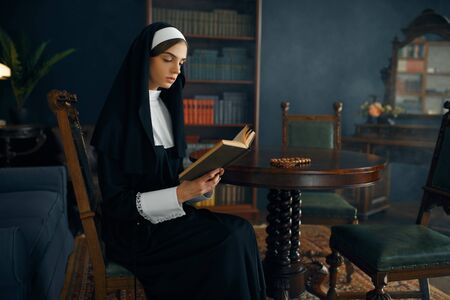 Young nun in a cassock reads a prayer Stock Photo