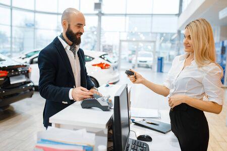 Female seller gives keys to man in car dealership Reklamní fotografie