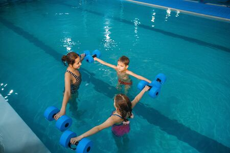 Children swimming group, workout with dumbbells