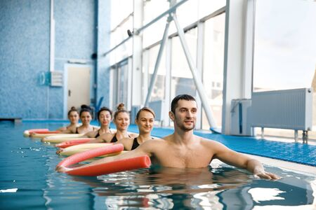 Instructor and swimmers group, training in pool