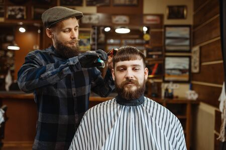Barber with comb and scissors makes a haircut