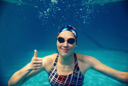 Female swimmer shows thumbs up underwater in pool
