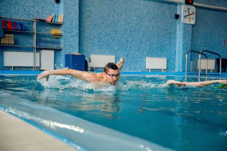 Male and female swimmers swims in the pool