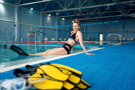 Female swimmer in flippers poses at the poolside