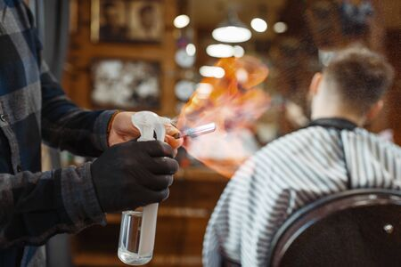 Barber processes the blade with fire, customer sitting in chair. Professional barbershop is a trendy occupation. Male hairdresser and client in hair salon