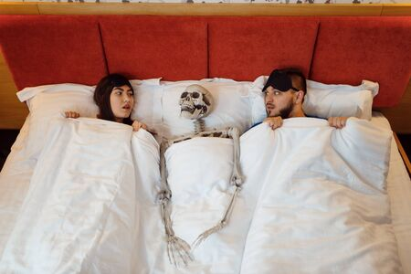 Husband, wife and skeleton lying in the bed