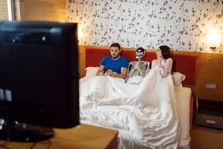 Husband watching TV, wife kissing human skeleton