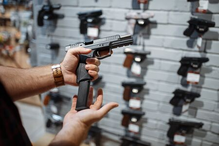 Man choosing new handgun at showcase in gun shop. Male person buying pistol for security in weapon store, selfdefence and sport shooting hobby Stock Photo