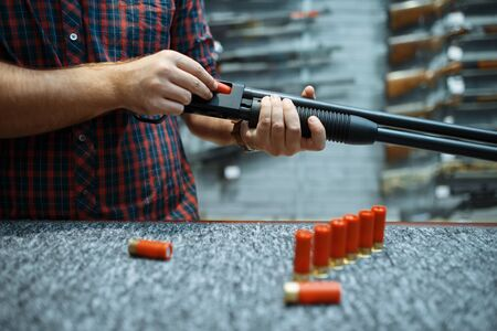Male person with rifle loads ammo at showcase in gun shop. Euqipment for hunters on stand in weapon store, hunting and sport shooting hobby