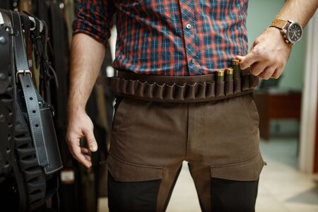 Man choosing ammo belt and uniform for hunting in gun shop. Euqipment for hunters on stand in weapon store, sport shooting hobby