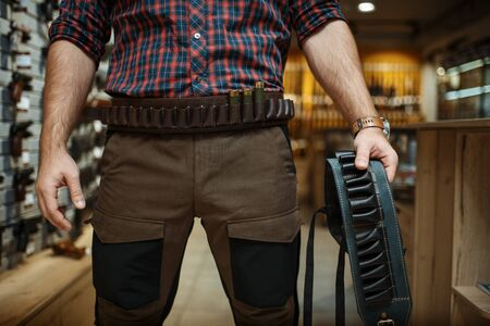 Man in hunting uniform holds ammo belt in gun shop. Euqipment for hunters on stand in weapon store, sport shooting hobby