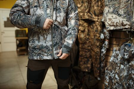 Man trying on uniform at showcase in gun shop. Euqipment and rifles for hunters on stand in weapon store, hunting and sport shooting hobby Stock Photo