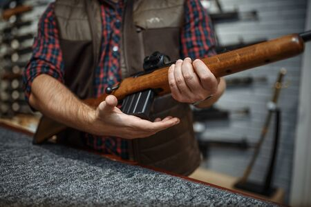 Man loads a rifle at counter in gun shop. Euqipment for hunters on stand in weapon store, hunting and sport shooting hobby