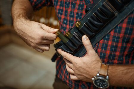 Man in ammo belt, rifles on background, gun shop. Euqipment for hunters on stand in weapon store, sport shooting hobby Stock Photo