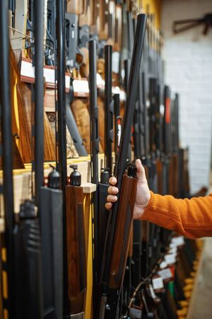 Man choosing rifle at showcase in gun shop. Euqipment for hunters on stand in weapon store, hunting and sport shooting hobby