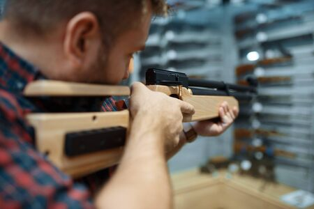 Male person with pneumatic rifle at showcase in gun shop. Euqipment for hunters on stand in weapon store, hunting and sport shooting hobby Stock Photo