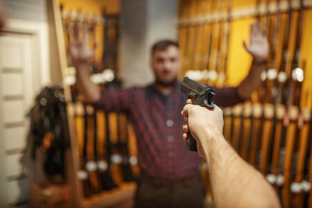 Man aims with new handgun on seller in gun shop. Male person buying pistol for security in weapon store, selfdefence and sport shooting hobby Stock Photo - 143380162