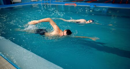 Male and female swimmers swims in the pool. Man and woman in the water, sport swimming skill training, motion view, workout before competition