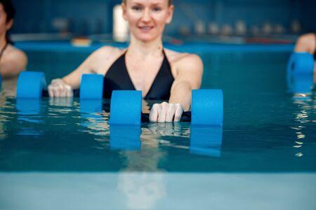 Female aqua aerobics, training with dumbbells