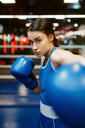 Woman in blue boxing gloves hits in camera
