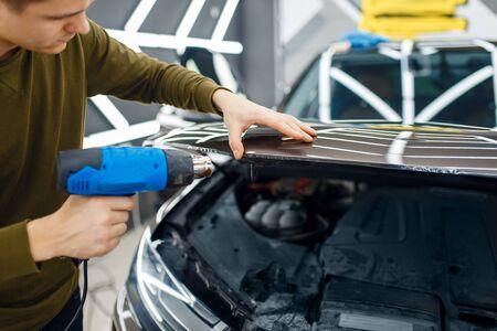 Männlicher Arbeiter trocknet Vinyl-Autoschutzfolie auf der Motorhaube. Anbringen einer Beschichtung, die den Lack des Autos vor Kratzern schützt. Neufahrzeug in Garage, Tuning-Vorgang Standard-Bild
