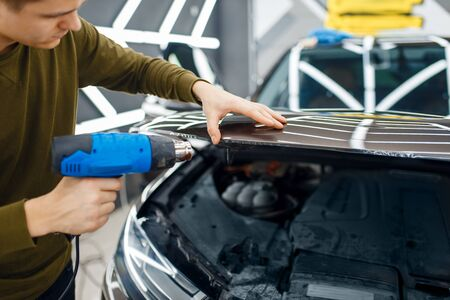 Male worker dries vinyl car protection film on hood. Installation of coating that protects the paint of automobile from scratches. New vehicle in garage, tuning procedure Banco de Imagens