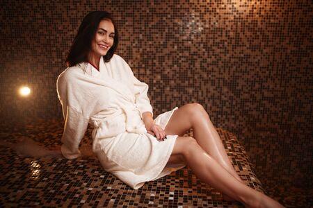 Woman sitting on a hot stone in hamam, sauna