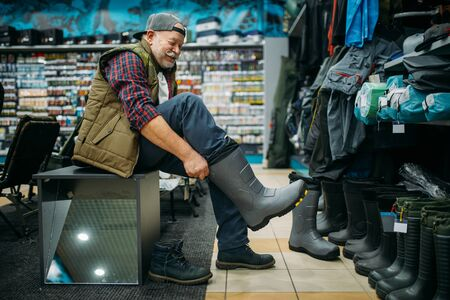 Fisherman tries on rubber boots in fishing shop