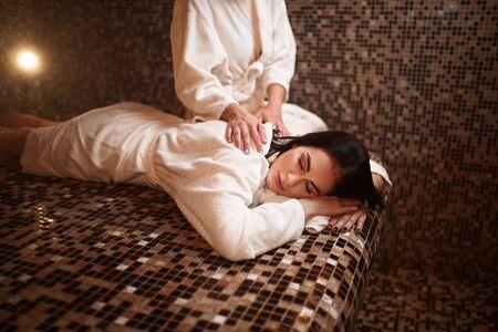 Une masseuse fait un massage à une femme dans un sauna