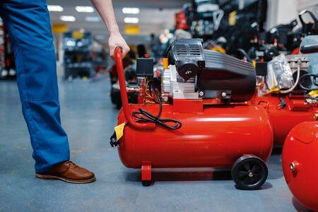 Worker choosing pneumatic compressor in tool store