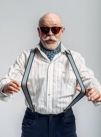 Fashionable elderly man, trousers with suspenders