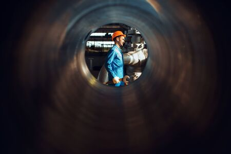 Worker with wrench on factory, view through tube Foto de archivo