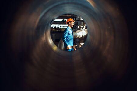 Travailleur avec clé sur usine, vue à travers le tube Banque d'images