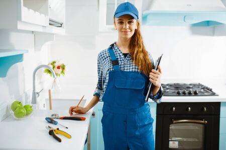 Female furniture maker in uniform holds notebook Stok Fotoğraf
