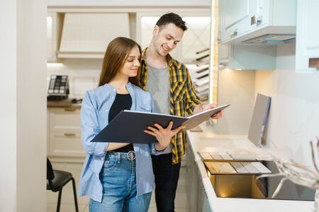 Couple choosing kitchen garniture, furniture store