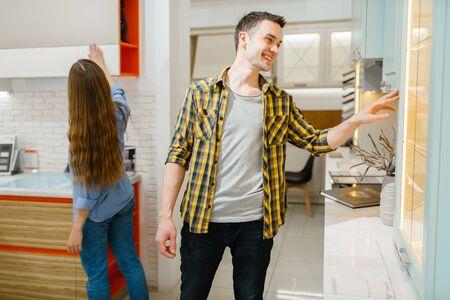 Couple buying kitchen garniture in furniture store