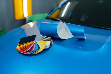 Car wrapping, protective vinyl foil or film color palette and installation tools on the vehicle closeup, nobody. Auto detailing. Automobile paint protection Foto de archivo