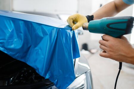 Car wrapping, man with drier installs protective vinyl foil or film on vehicle hood closeup. Worker makes auto detailing. Automobile paint protection coating, professional tuning Banco de Imagens