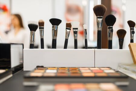 Shelf with shadows and brushes in cosmetics store, nobody. Luxury beauty shop, showcase with products in fashion market