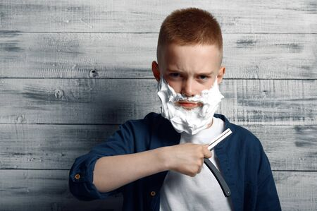 Boy with shaving foam on his face holds a razor