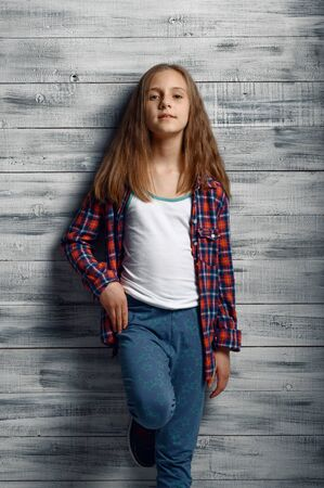 Adorable little girl standing at wall in studio
