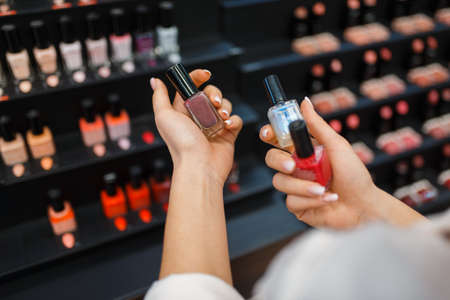 Woman takes lipstick from shelf in cosmetics store. Buyer at the showcase in luxury beauty shop salon, female customer in fashion store