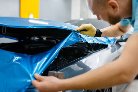 Car wrapping, man cuts protective vinyl foil or film on vehicle hood closeup. Worker makes auto detailing. Automobile paint protection coating, professional tuning Stock Photo