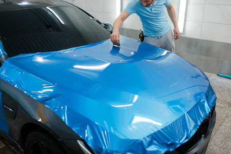 Car wrapping, man with squeegee installs protective vinyl foil or film on hood. Worker makes auto detailing. Automobile paint protection coating, professional tuning