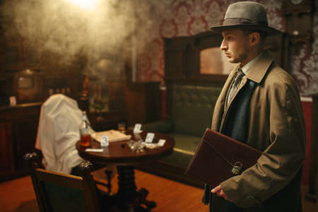 Puzzled detective in coat and hat, crime scene