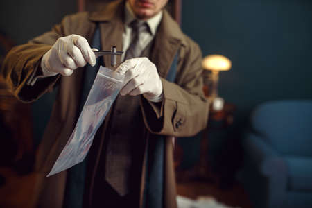 Male detective with tweezers finds sleeve Imagens