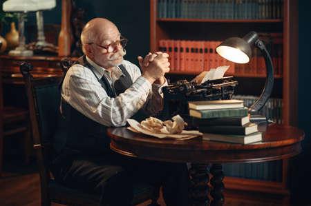 Elderly writer thinks at vintage typewriter Stock Photo