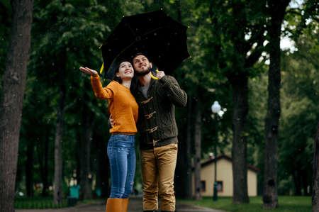 Happy love couple enjoys summer rainy day