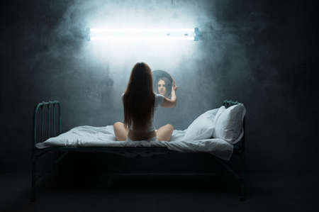Mad woman with mirror sitting in bed, insomnia